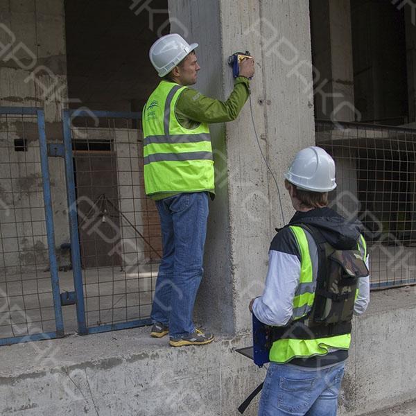 Геофизик и помощник обследуют бетонную конструкцию